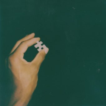 Photograph of a hand holding a puzzle piece